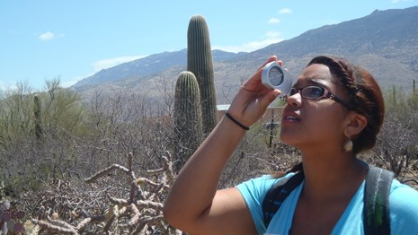 A woman looks through a measuring device in a desert landscape