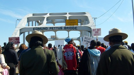 Rangers in flat hat mingle with large group walking across steel arch bridge