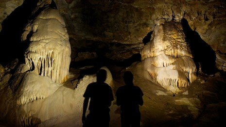 Visitors silhouetted in flashlight beams, cave formations illuminated