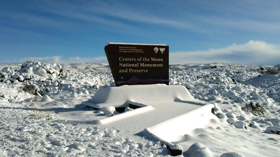 snow covered entrance sign