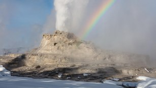 Snow-covered geyser erupting