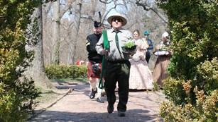 Ranger carrying shamrocks in a process of people that includes an Irish flag-bearer