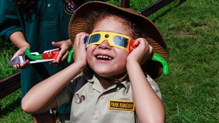 Kid wearing a park ranger costume wearing filtered glasses while looking up