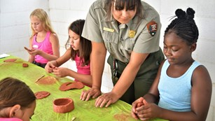 Ranger talking to kids making pottery