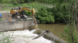 An aerial view of the excavator crew notching the Brecksville Diversion Dam from day 1 of demolition