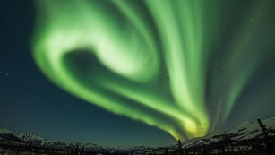 the northern lights swirl through a night sky