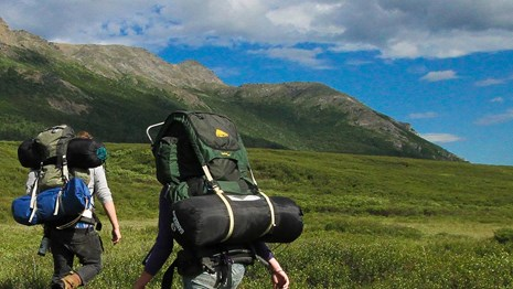 two backpackers trek across a grassy valley