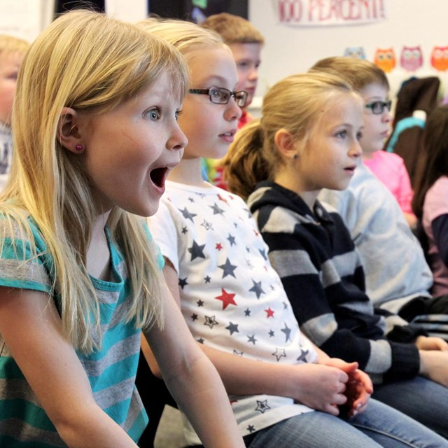 students watch a distance learning program excitedly