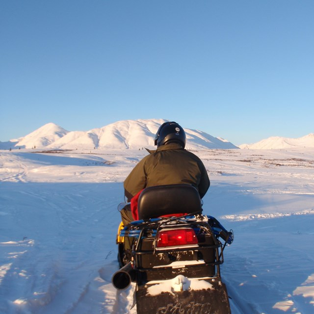 a person riding a snowmobile in a snowy, mountainous landscape