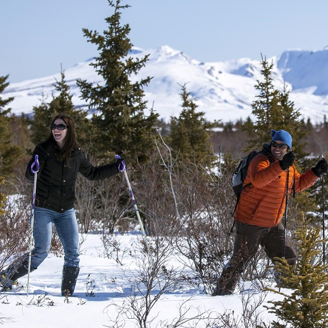 a man and woman hike using snowshoes