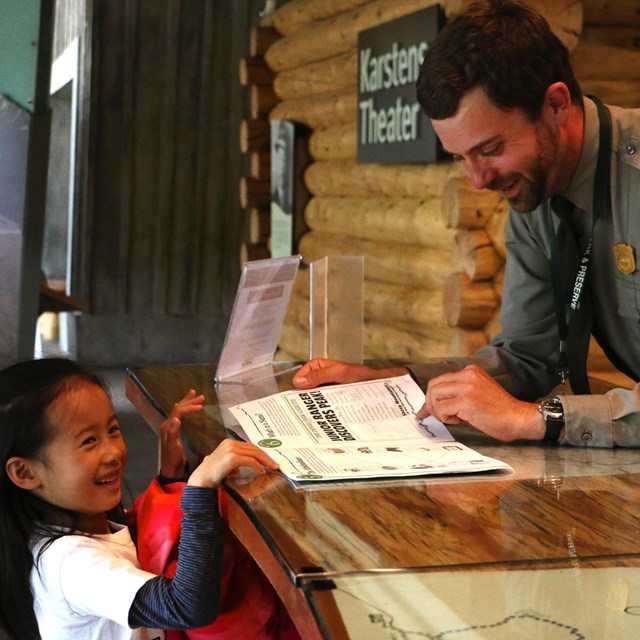 a girl smiles as a park ranger checks her junior ranger book