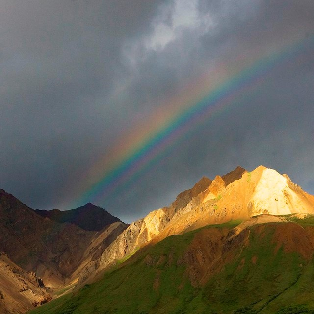 a rainbow shines behind a rocky ridge