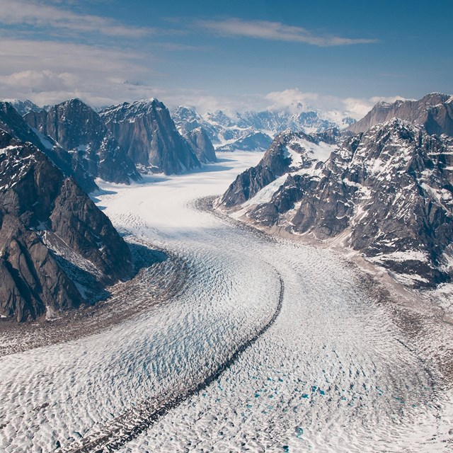 aerial view of a massive glacier flowing out of craggy mountains