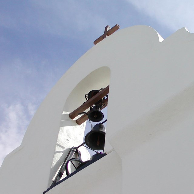 A bell tower of a white stucco church.