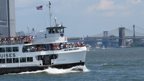 A Statue Cruise ferry makes its way across the harbor, the Brooklyn Bridge is in the backround
