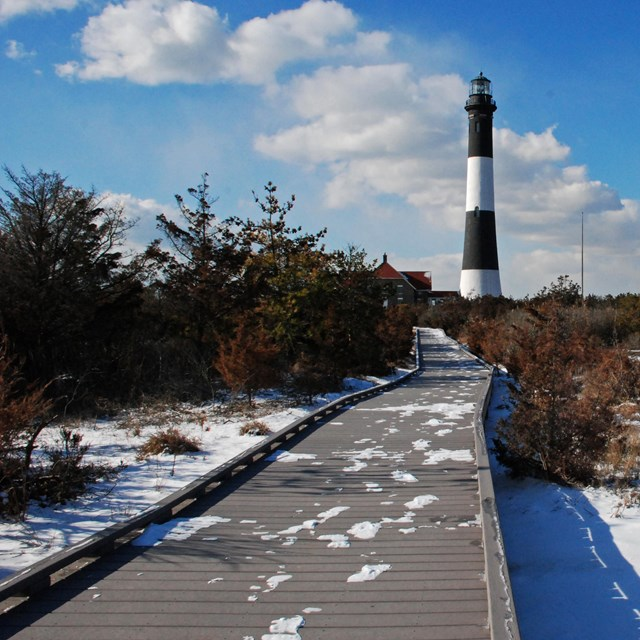 A snowy boardwalk leads to a black and white lighthouse tower.