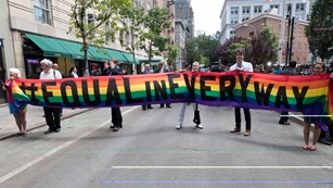 Group of people standing with long rainbow banner that says