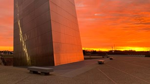 Base of a tall metal structure on a plaza turning red with the sunset