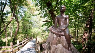 Bronze statue of boy sitting on rock gazing up
