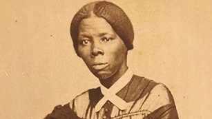 Sepia portrait of young Harriett Tubman seated in chair