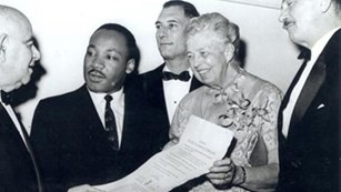 Eleanor Roosevelt standing with Martin Luther King Jr. holding document