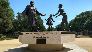A statue of Mary McLeod Bethune handing her legacy to two young children.