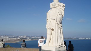 Tall white statue of Cabrillo with shoreline in background.