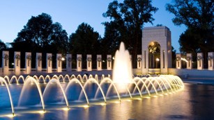 Memorial pillars surrounding a large fountain at night