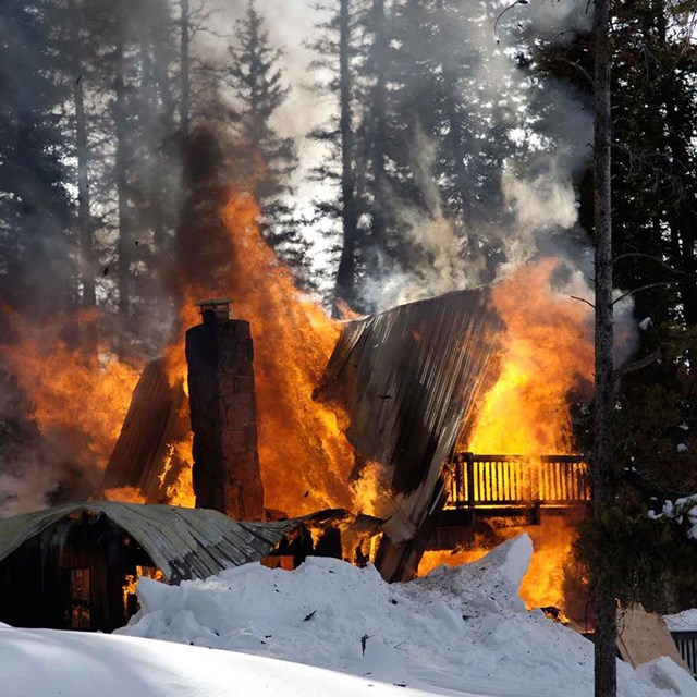 burning cabin in the woods in the winter
