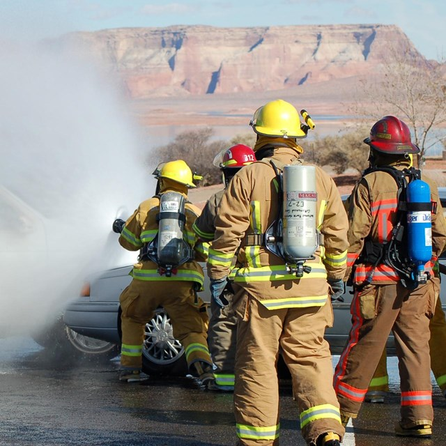 NPS firefighters use a fire hose to put out a vehicle fire during training