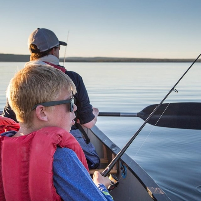 Child fishing on boat with life jacket.