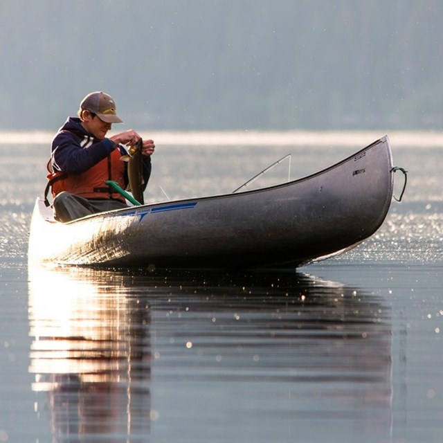 man in canoe on water holding a newly caught fish.