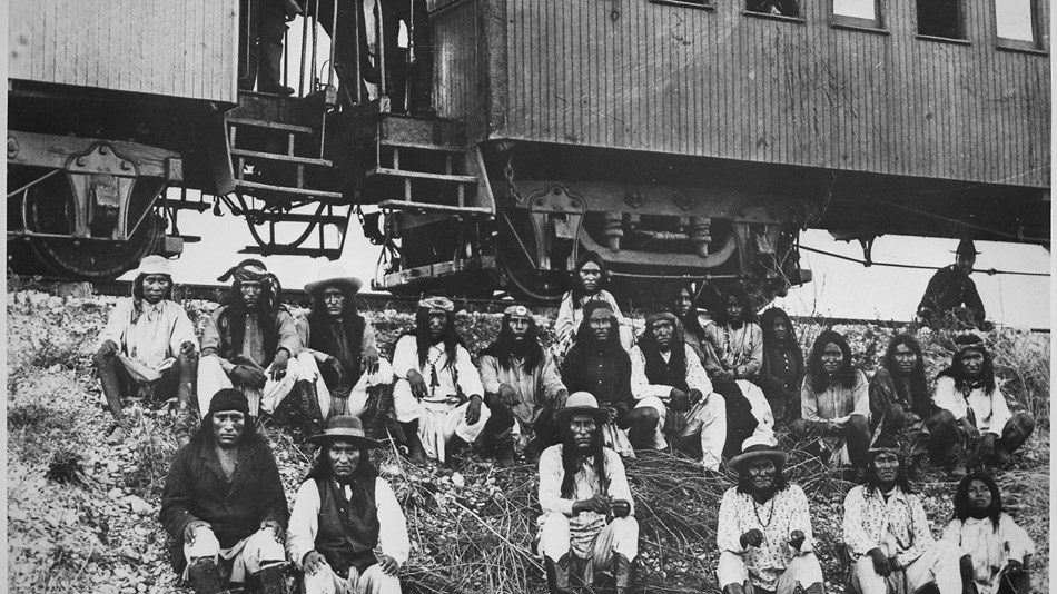 Chiricahua Apaches sit outside of a railway car bound for Florida