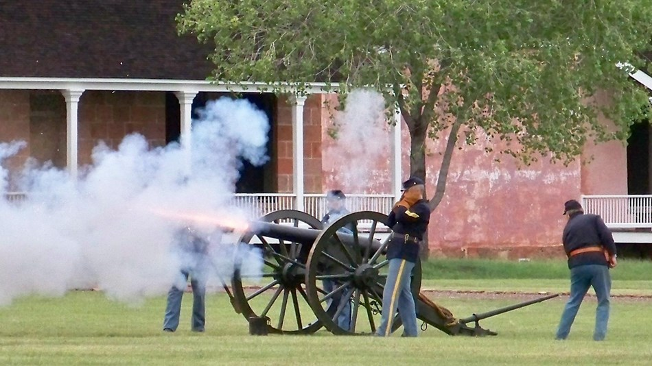 Artillery firing on the parade ground. Smoke billows from the 3 inch ordnance rifle.