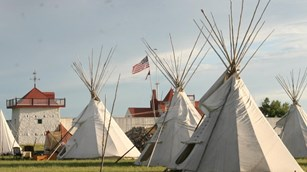 Canvas tipis in foreground with red roofed bastion in the rear.