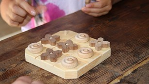 Child playing with wooden Tic-tac-toe board