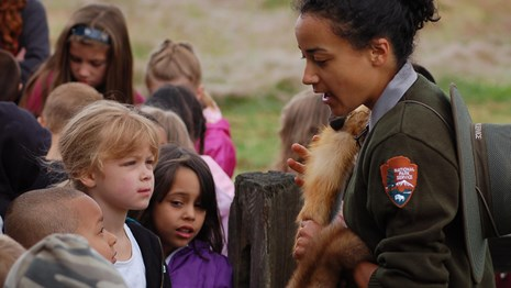 Photo of park ranger holding a beaver fur with children.