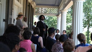 An actor dressed as Frederick Douglass talks to a crowd