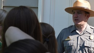 A group of students interacts with a ranger outside a historic house