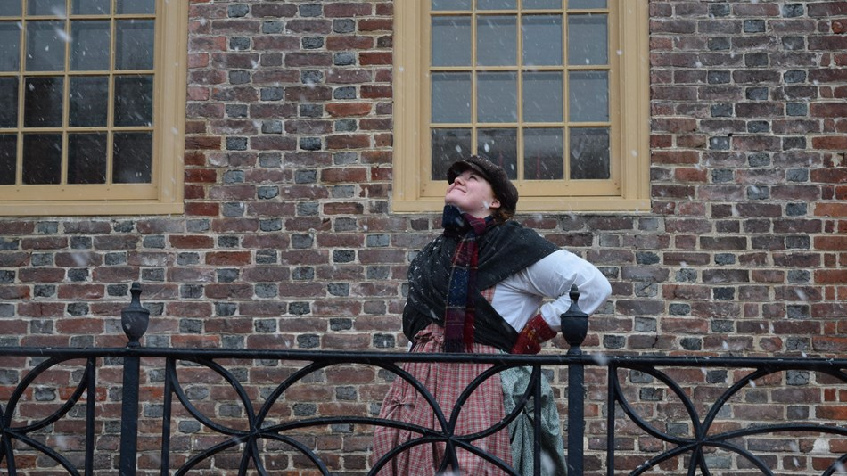 A women in colonial clothing looks up at the snow
