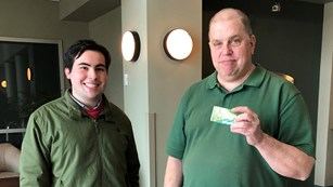 The park's volunteer coordinator hands a volunteer their free Volunteer-In-Parks Pass.