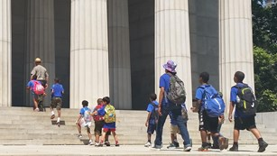 Ranger and students walking up steps in front of large columns of Mausoleum