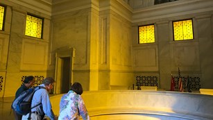 A Park Volunteer talks with visitors inside the Mausoleum