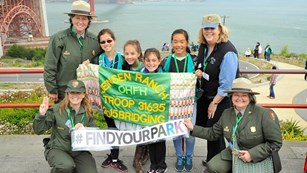 Girl scouts posing with park rangers and a sign reading