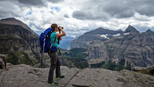 a hiker on a mountaintop looks through binoculars as dark clouds approach