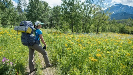 A person stands on a trail with a big backpack surrounded by grass.