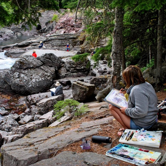 Woman sits by stream and paints with watercolor, other painters in background