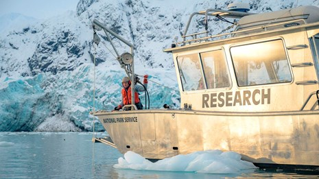 A park ranger works a rope pulley device on a research boat in front of Margerie Glacier