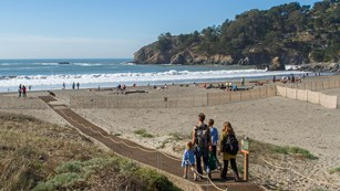 People walking down accessible sand mat onto muir beach with the blue ocean beyond
