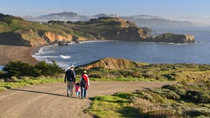 A couple with small child walk down a road with Rodeo Beach, ocean, Bird Rock and city behind